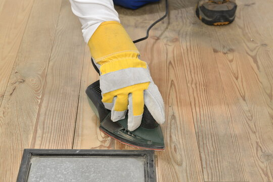 Carpenter's hand sanding with electrical sander