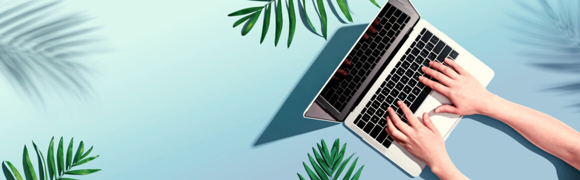 Person using a laptop computer with tropical leaves from above