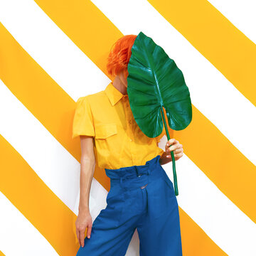 Unrecognizable Model holding palm leaf and wearing vintage look on trendy striped yellow background. Minimal fashion spring summer concept. Stylish colours combination.