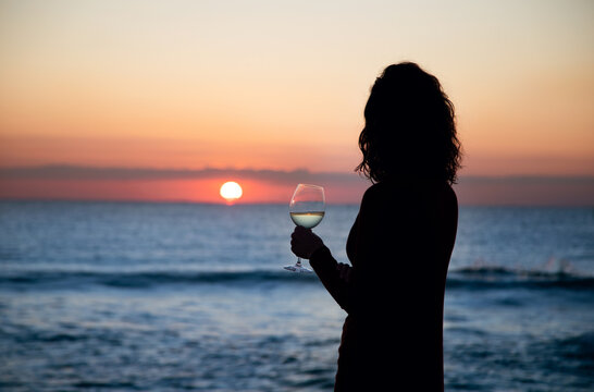 girl has a glass of wine in front of the sea at sunset