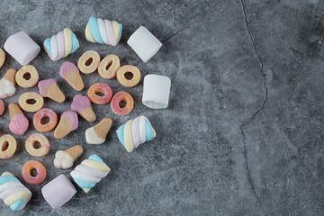 Fototapeta Mix of marshmallow and jellybeans on the marble background obraz