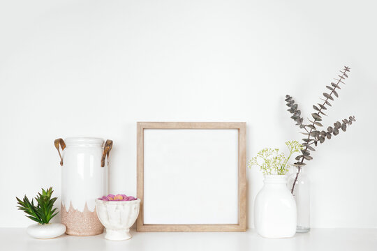 Mock up square wood frame with home decor, plants and flowers. White shelf against a white wall. Copy space.