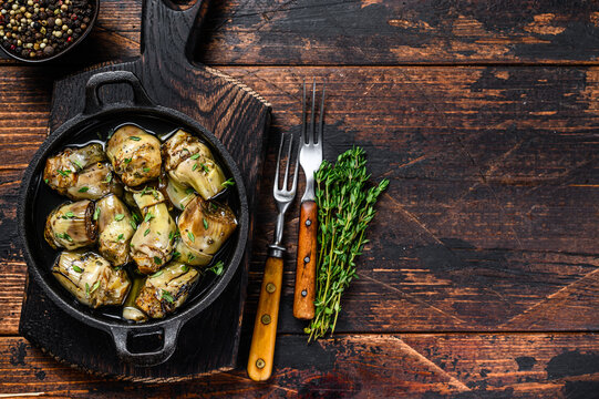 Marinated artichokes in olive oil in a pan. Dark wooden background. Top view. Copy space