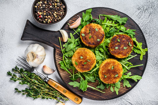 Veggie patty cutlet with lentils, vegetables and arugula. White background. Top view