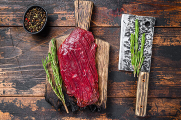 Venison raw meat steak on a cuuting board with rosemary. Black background. Top view