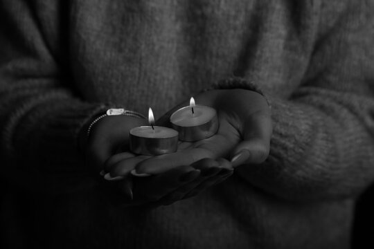 two candles in female hands in black and white