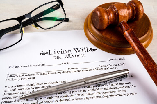 Living will declaration form with pen, gavel and striking block and glasses on top.