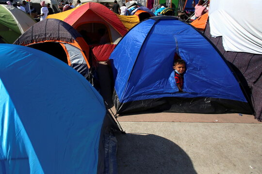 A child looks out from a tent next to other migrants from Central America who are camping outside the El Chaparral border crossing, hoping to cross and request asylum in the U.S. , in Tijuana