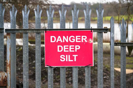 Danger deep silt danger sign on fence at nature reserve