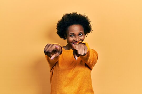 Young african american woman wearing casual clothes pointing to you and the camera with fingers, smiling positive and cheerful