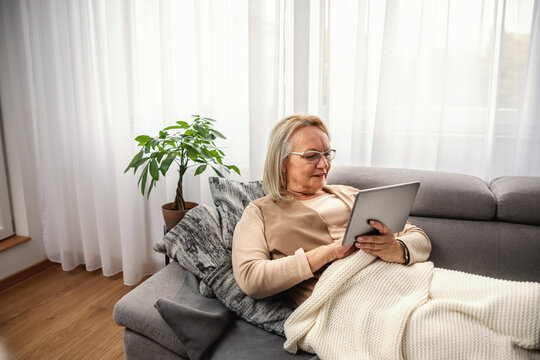 Smiling blond senior woman sitting on sofa and using tablet for online advices.