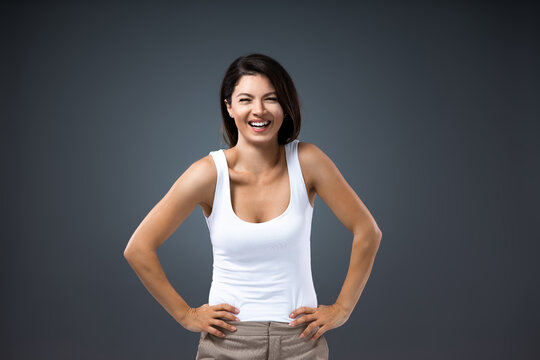 Young smiling attractive woman standing with hands on hips and looking at camera.