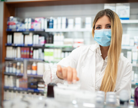 Female pharmacist checking the inventory in a pharmacy while wearing a coronavirus covid mask