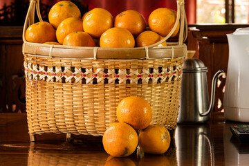 Fototapete - Ripe oranges in a bamboo basket on a wooden table.