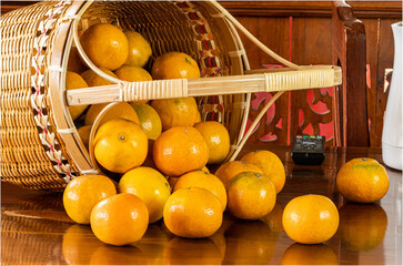 Fototapete - View of oranges in a bamboo basket on wooden table.