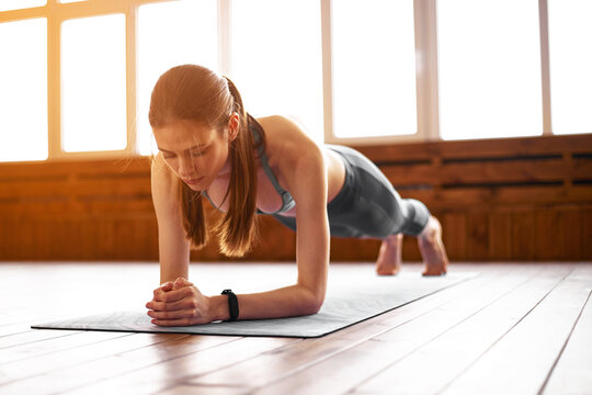 Fit woman working on abdominal muscles doing plank exercise