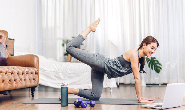 Portrait of sport asian woman in sportswear sitting relax and practicing yoga and do fitness exercise with laptop computer in bedroom at home.Diet concept.Fitness and healthy lifestyle