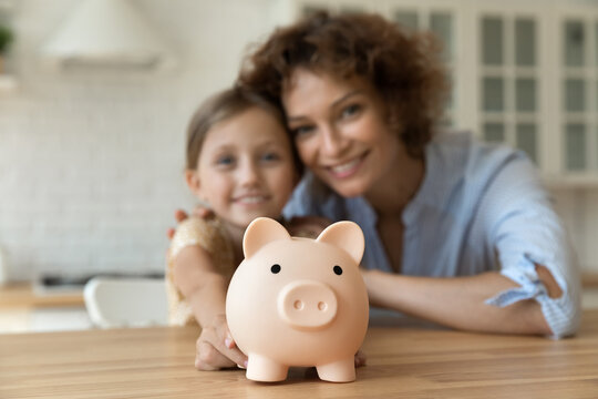 Take care of future. Blurred portrait of smiling young mother small girl daughter look at camera show funny pig for coins offer you to make bank deposit save money. Focus on piggybank on kitchen table