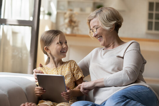 Sharing secrets with granny. Happy little girl talk with loving mature grandmother on sofa hold tablet show video game. Laughing grandma hug small grandkid discuss funny photo at social network on pad
