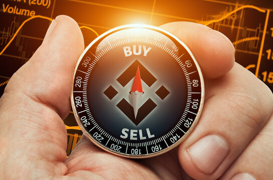 Male hand holding compass with binance coin in front of stock market chart data. Compass needle showing buy word. Cryptocurrency trading concept.