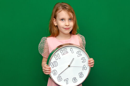 Girl holds a large clock in her hands.