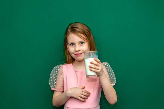 Baby girl holding a glass of milk in her hands
