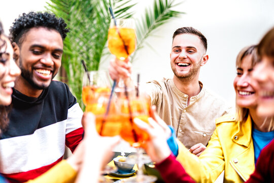 People toasting spritz at cocktail bar restaurant - Life style concept with young friends having fun together sharing drinks on happy hour at garden party - Bright warm filter with focus on right guy