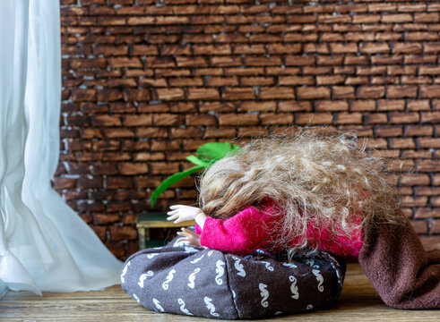 Crying doll with long brown hair on a floor pillow against a brick wall in a dollhouse.