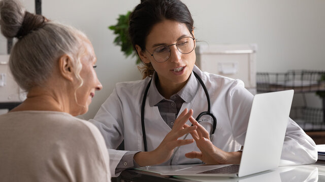 Close up professional female doctor wearing uniform and glasses consulting mature patient, talking, using laptop, explaining prescription, discussing treatment, medical checkup result in hospital