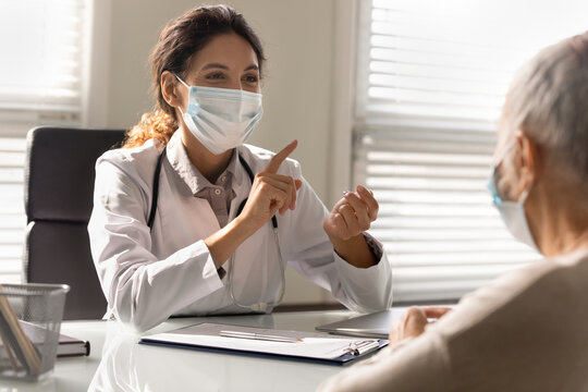 Close up smiling female doctor wearing medical face mask consulting mature patient at meeting in hospital, happy therapist physician and senior woman discussing checkup or treatment results