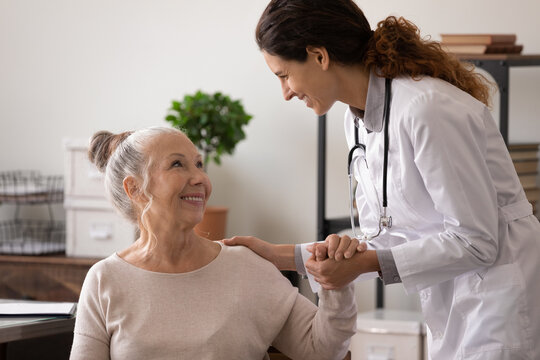 Smiling mature patient and caring female doctor holding hands, discussing good news, successful treatment, caregiver wearing uniform supporting senior woman in hospital, psychological help concept