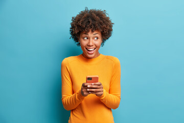 Positive curly haired ethnic woman uses mobile phone checks messages and reads news holds modern...