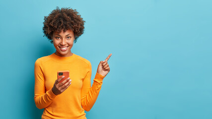 Fototapeta Horizontal shot of happy dark skinned Afro American woman enjoys mobile communication and modern technologies poses against blue background points away on free space for your advertising content obraz