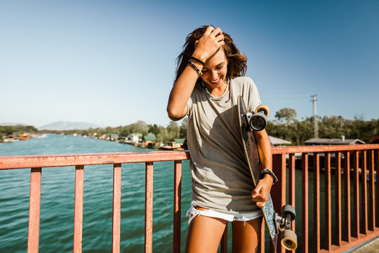 Beautiful and fashion young woman posing with a skateboard.
