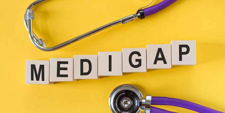Word MEDIGAP building from wooden cubes on yellow desk with stethoscope.