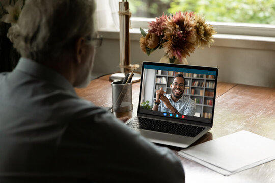 Screen view of mixed race young man talking to mature father. Old man 60s uses laptop for video call, chatting online with adopted son. Senior male student watching webinar, teacher speaking at webcam