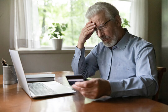 Upset senior 60 - 70s aged man worried about finance safety data, online payment security. Mature retired grey haired male bank client concerned about problem with credit card, financial fraud threat