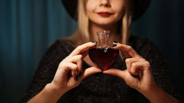 Cropped image of woman holding heart shaped glass jar of love potion. Beautiful young woman in a witch hat