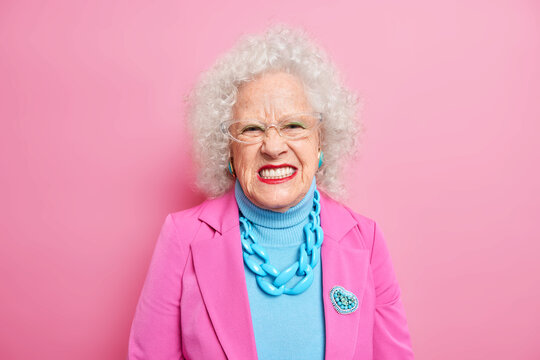 Portrait of angry curly haired senior woman squints face and looks unhappily at camera expresses negative emotions wears elegant costume with necklace and brooch red lipstick transparent glasses
