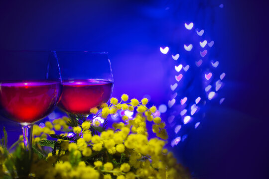 Mimosas and two glasses of red wine on a blue background with blurred lights in the shape of little hearts