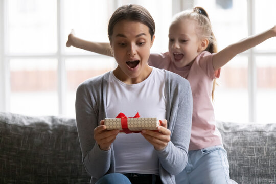 Excited daughter girl giving birthday gift box to amazed mum. Happy surprised mommy receiving present wrap from preschooler kid. Family celebrating mothers day. Congratulation, special date concept