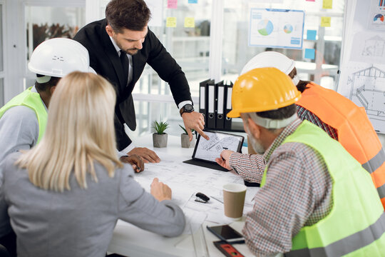 High-skilled purposeful multiracial team of engineers in special uniforms and male and female managers, brainstorming together over joint building project, looking at the tablet screen