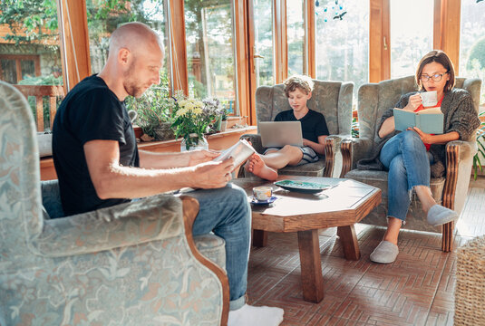 Mother, father and son family sitting together in Sunroom in cozy armchairs and reading books, using a laptop, and enjoying togetherness. Pandemic lockdown, home office and stay-at-home concept image.