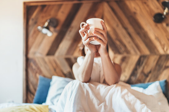 "Lazy female lying down under the white blanket on the linen bed and holding the fresh coffee cup in the early morning. Lazy day off and ""coffee in bed""concept image."