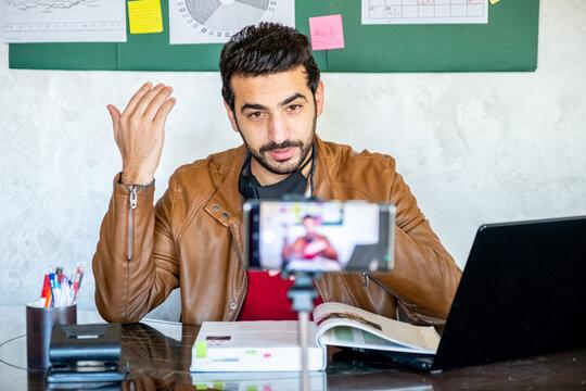 Happy male coach teacher webinar speaker looking at camera givin
