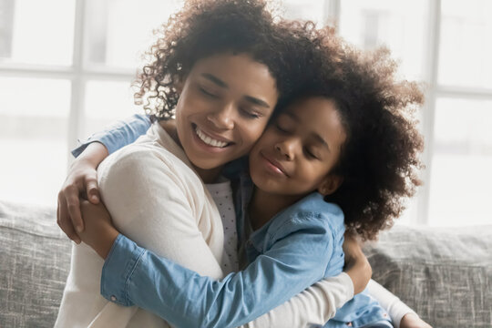 Portrait of happy mum with shut eyes embracing daughter girl. Affectionate Black mother and kid expressing love, hugging, spending good time together at home. Family, affection concept. Close up