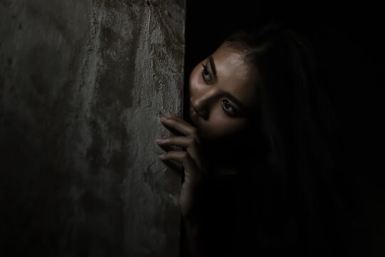 Scared woman hiding behind wall in dark room Young crazy scared and shocked asian woman escape murderer and get frightened Copy space Facial expression, human emotion concept Looking horror Halloween
