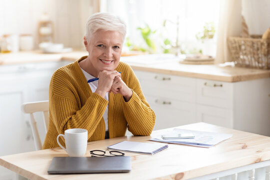 Positive elderly lady freelancer working from home or studying