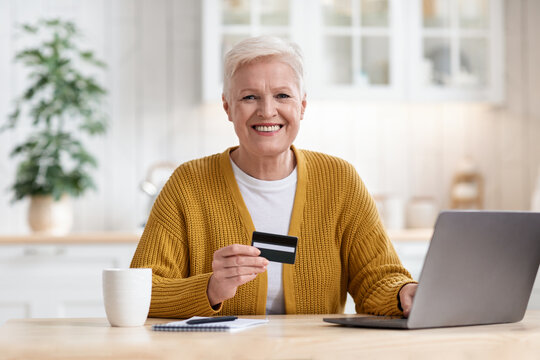 Happy aged lady holding credit card and using laptop