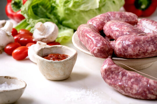 Raw uncooked italian sausages salsiccia in plate on white marble table. Green salad, vegetables and tomato sauce around.